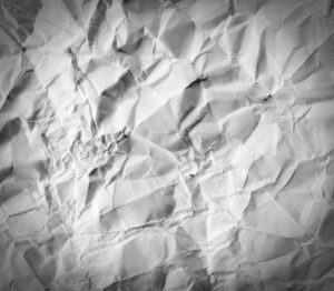 Crumpled up paper background representing wasted paper with traditional time clock systems.
