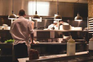 Kitchen staff preparing food clocked in using fingerprint time clocks for restaurant employees.