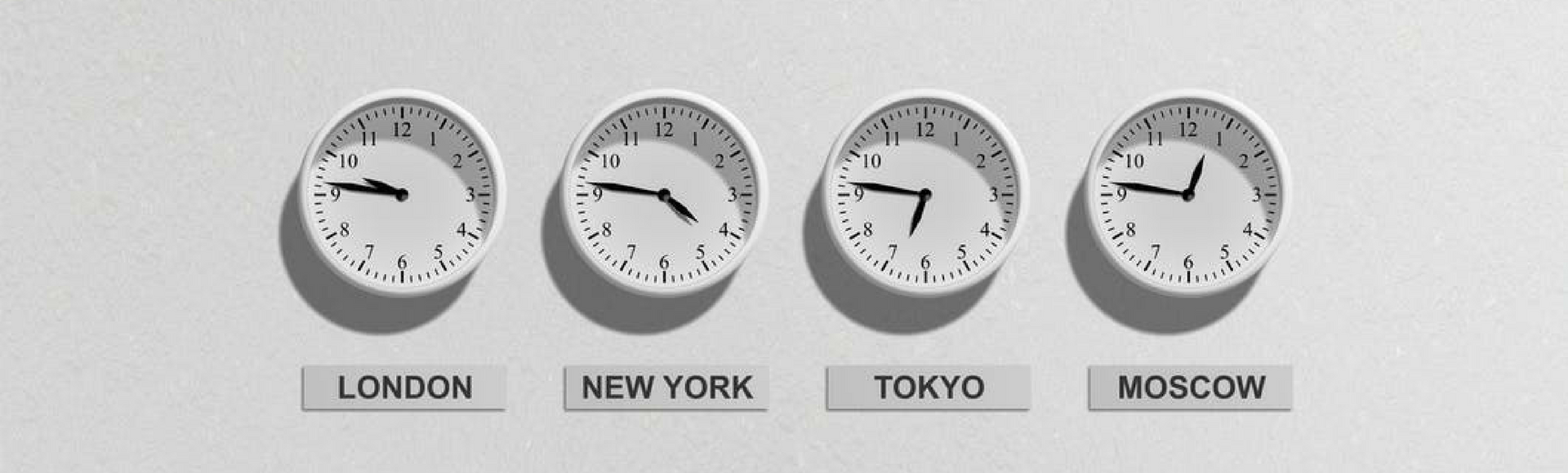 White time clocks displaying time in four different regions mounted on white wall representing saving time with global workforce by using an online time clock system.