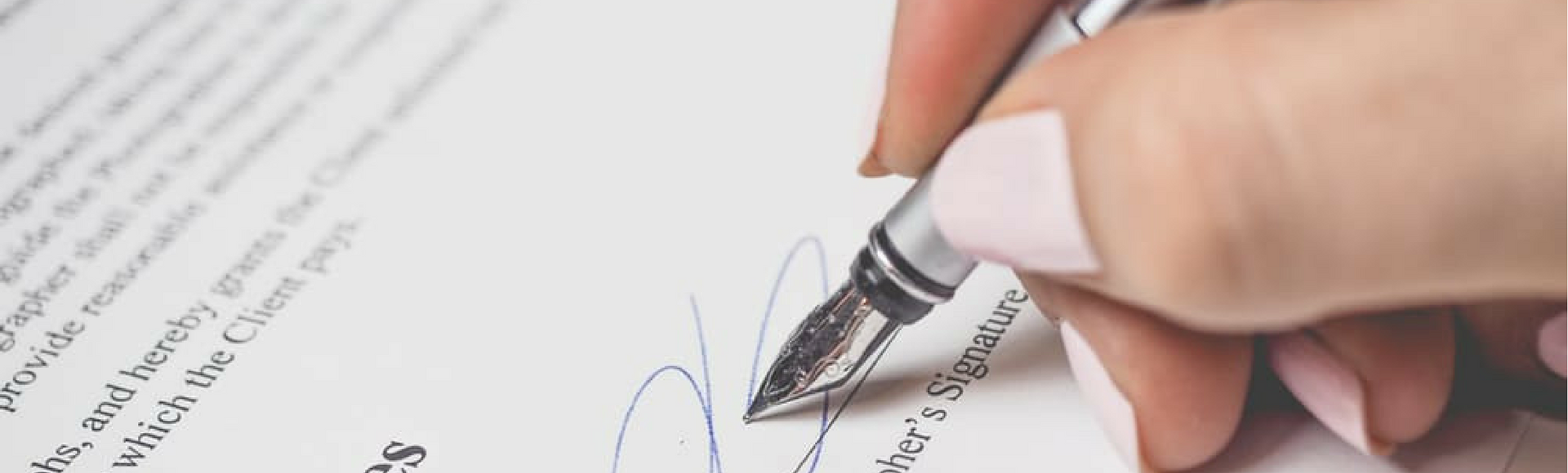 Person Holding Silver Pen Signing Employer's Signature, which never happens at FingerCheck which operates contract-free.