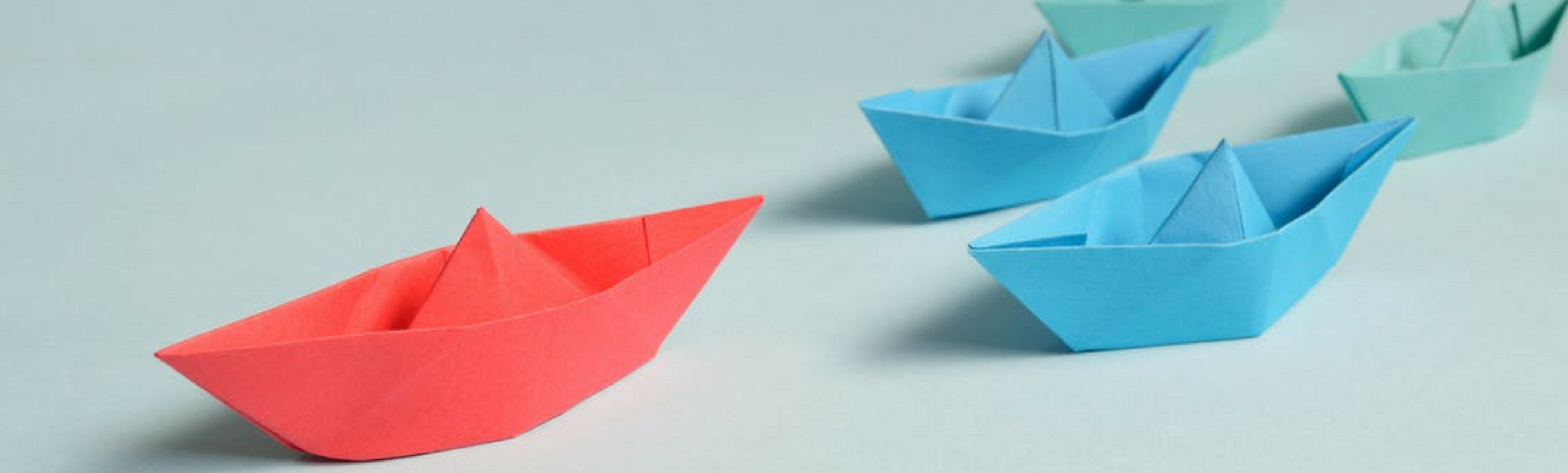 Small red oragami boat leads the way for blue boats and green boats behind it, reflecting show-don't-tell leadership tactics.
