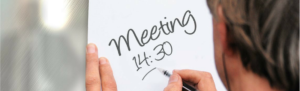 Manager writes meeting time on dry erase board in leading employees in time management.