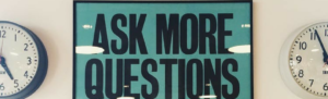 "Sign displaying ""Ask More Questions"" between two time clocks suggests finding out more information about Fingercheck."