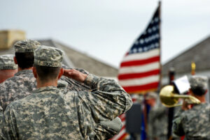 A soldier salutes veterans in front of the U.S. flag for Memorial Day.
