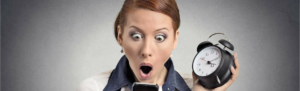 (Surprised) business woman with alarm clock looking at smartphone with Fingercheck alert notifications of punches for employee through email, text message, and punch notification.
