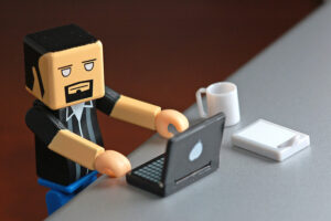 Mini lego figure at desk with laptop typing to demonstrate an employee looking at Fingercheck's table of local overtime laws.