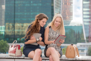 Two young women looking at a tablet together outdoors seated on the ledge of an office building, building in the background, showing that the slow summer season can actually be a great time for productivity.