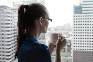 Dejected employee drinking coffee on office break after pay has been docked for being tardy.