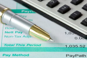 Calculator, payroll reconciliation figures and pen.