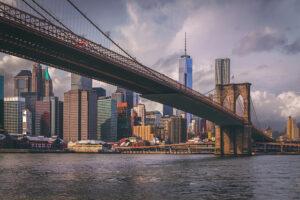 New York's Brooklyn Bridge with skyline beyond the horizon.