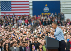 President Obama stands at podium with large crowds and U.S. flag backdrop announcing landmark policy extending overtime pay to 4.2 million salaried workers.