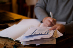 Payroll specialist sits with pile of paperwork.