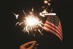 A girl's hand holds a sparkler and the U.S. flag.