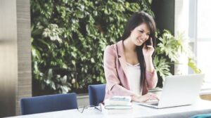 Woman on the phone working on laptop setting up rewarding activities for employees.