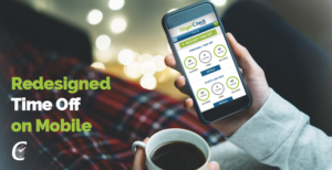 Woman sitting at home in pajamas with coffee cup looking at smartphone viewing Fingercheck's new and improved employee time off interface.