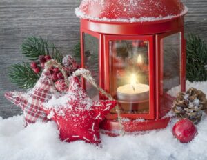 Beautiful red lantern with star Christmas ornaments in snow, lighting the way for small business owners to heed Fingercheck holiday tips.