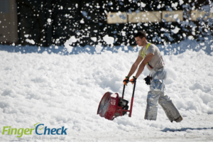 Male employee works clearing snow during winter weather blizzard.