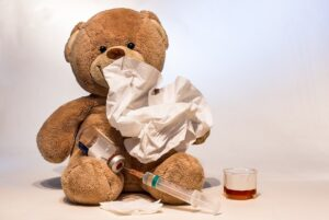 Sick teddy bear with thermometer, tissue and medicine symbolizing sick time under U.S. sick leave laws.