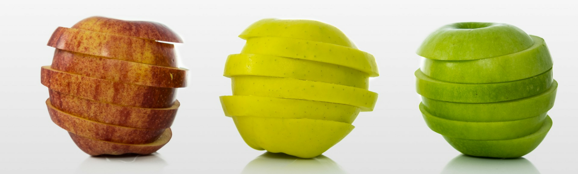 Three brightly colored apples sliced and spinning against white background to represent superfoods that are nutritious and help bosses and employees be at their most productive.