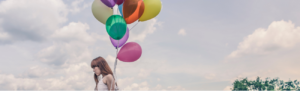 Young woman holds colorful floating balloons as symbol of floating holidays.